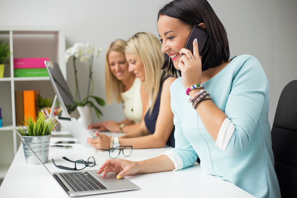 women-in-business-taking-order-on-phone-while-checking-website-on-laptop.jpg