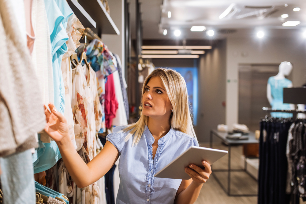 woman-browsing-clothing-products-in-boutique-while-working-on-ipad.jpg