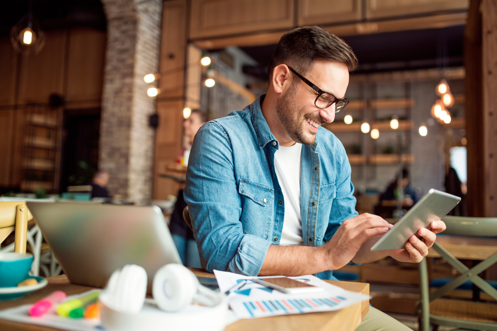 young-man-working-starting-digital-business-from-multiple-devices-in-cafe.jpg