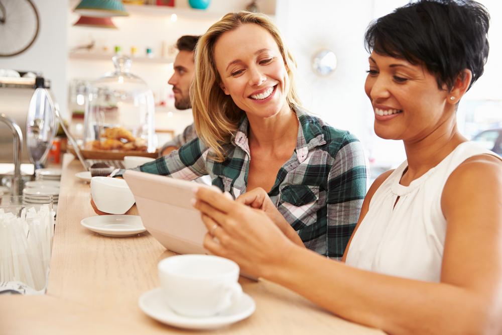 two-women-in-cafe-on-tablet-talking-small-business-idea-happy.jpg