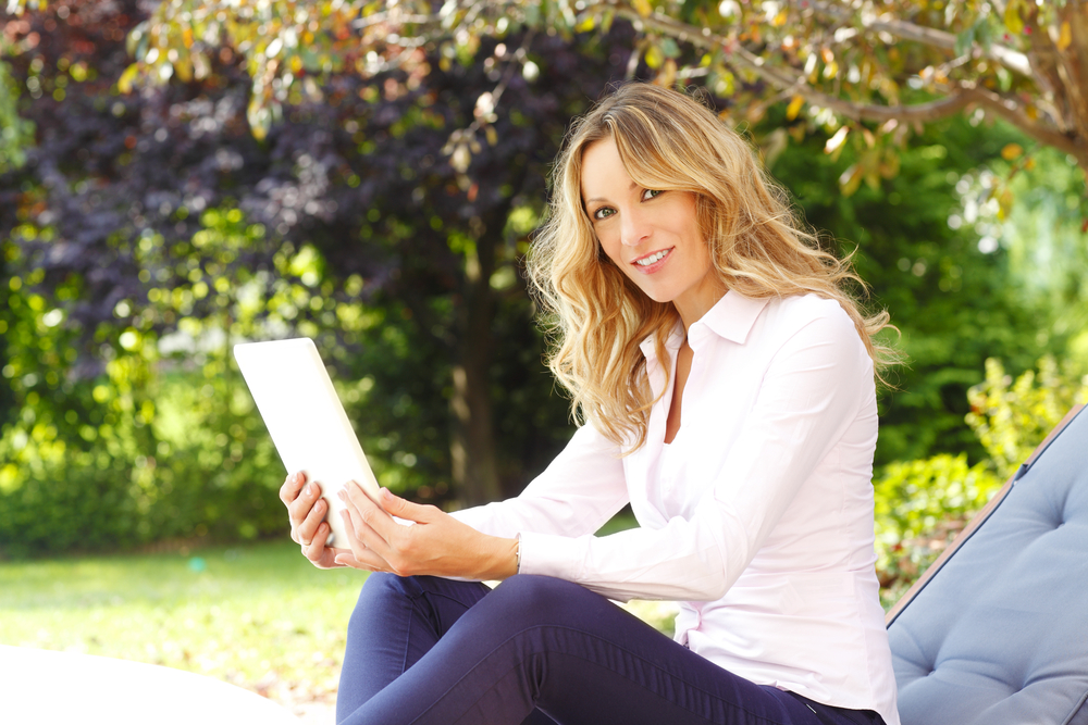 pretty-lady-sitting-in-park-working-on-tablet-online-business-happy.jpg