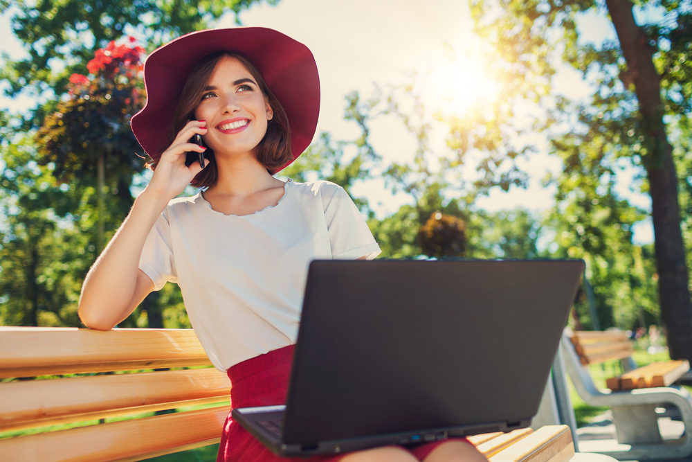 blogger-girl-on-mobile-phone-and-working-laptop.jpg