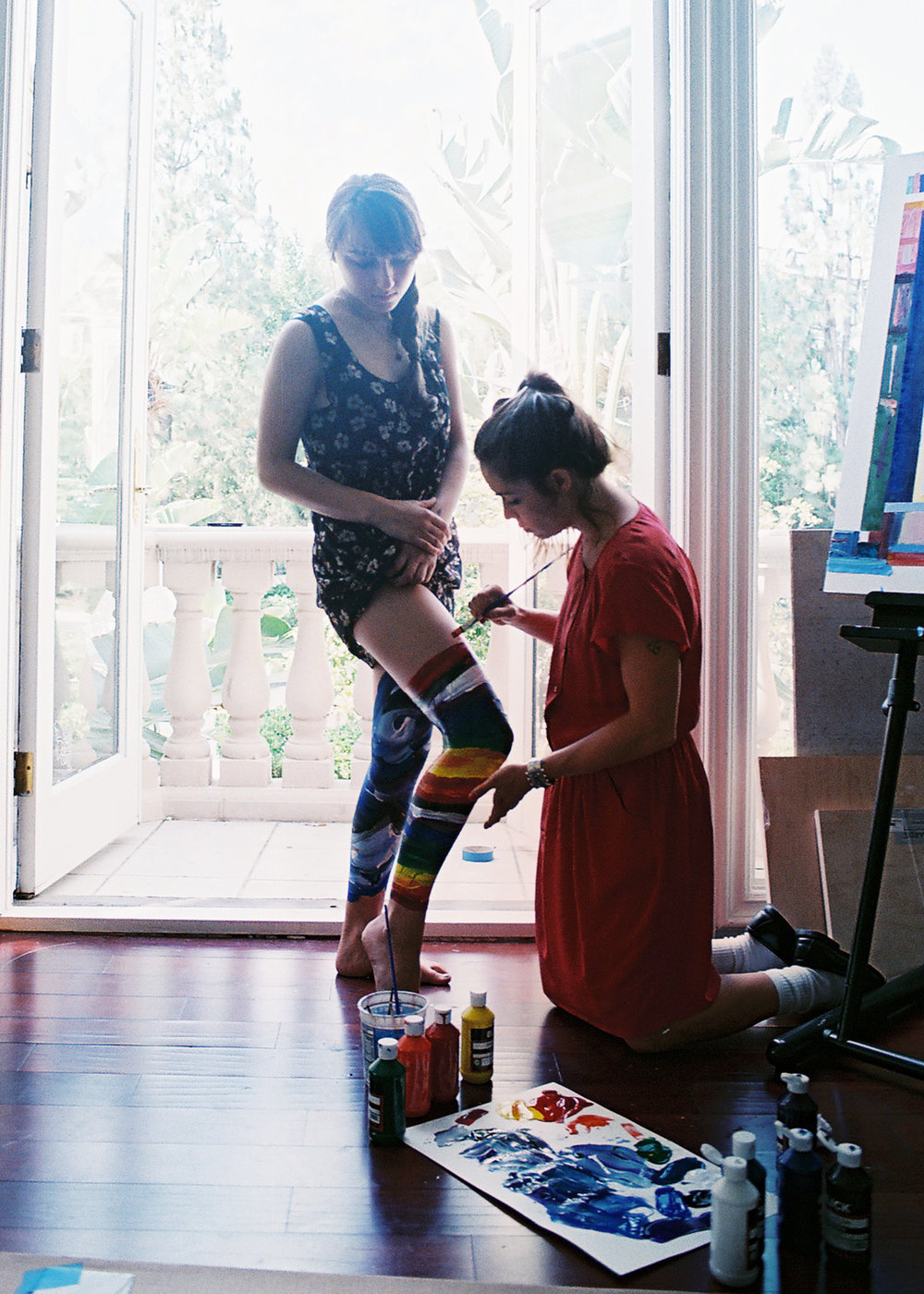 Lola painting Kendra by window on knees.jpg