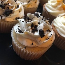 Cookies and Cream - Vanilla cake baked with Oreo cookie crumbs, topped with a vanilla butter cream frosting and garnished with Oreo cookie crumbs.