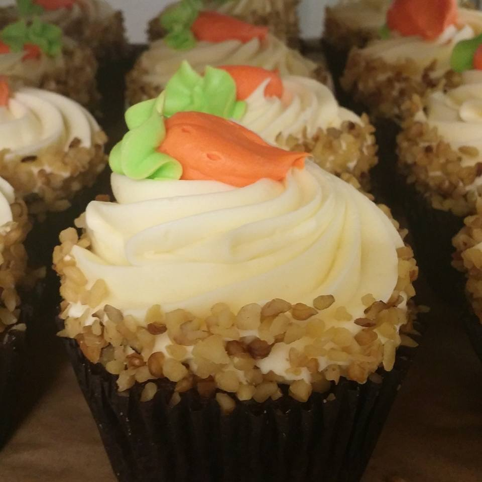 What's Up Doc?(Fall Flavor) - Carrot cake baked with carrots, raisins and walnuts, topped with a cinnamon cream cheese frosting, garnished sides with crushed nuts and a decorated butter cream carrot on top.