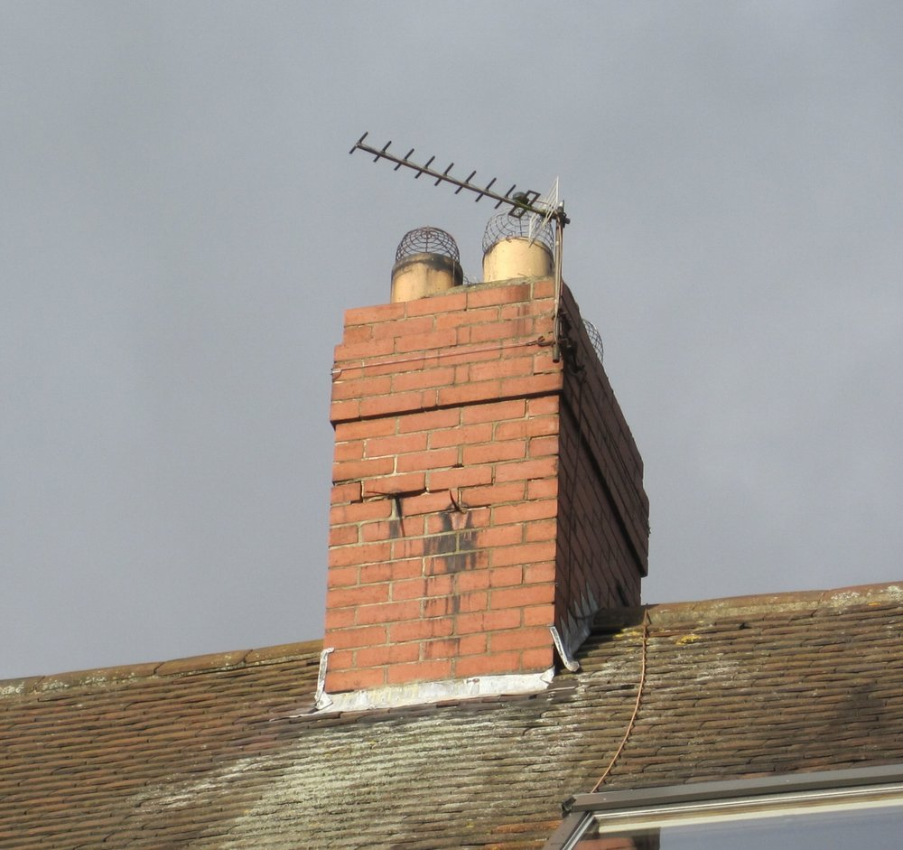 An uplifted chimney flashing and loose bricks with blown mortar pointing caused by expansion of old metal brackets.