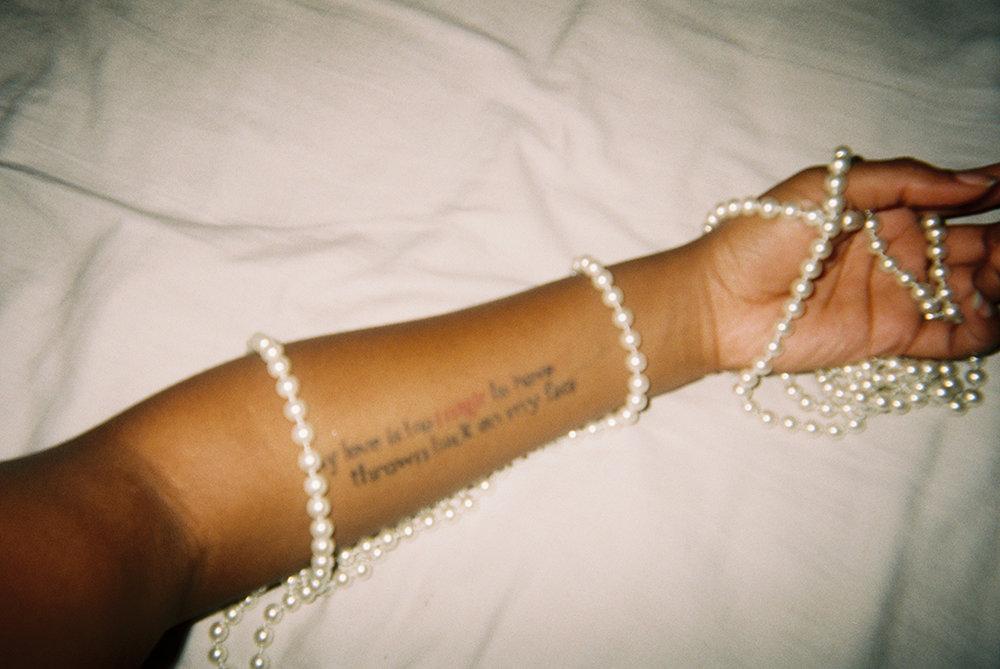 my love is too     My femininity does not have to be pearls and curls. My tattoo could be considered manly, but if you look closer, it's a celebration of my black womanhood.      'my love is too'   Mi feminidad no se define por perlas y colochos. Muy varonil puede ser percibido mi tatuaje pero si lo miras de cerca, te darías cuenta que es una celebración de la mujer afro-americana en mí.
