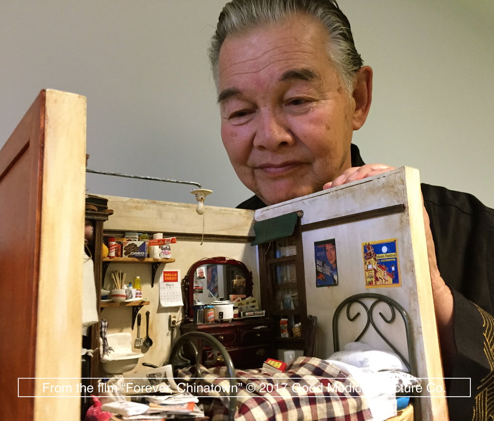 "Artist Frank Wong with the ""Single Room Occupancy"" miniature model."