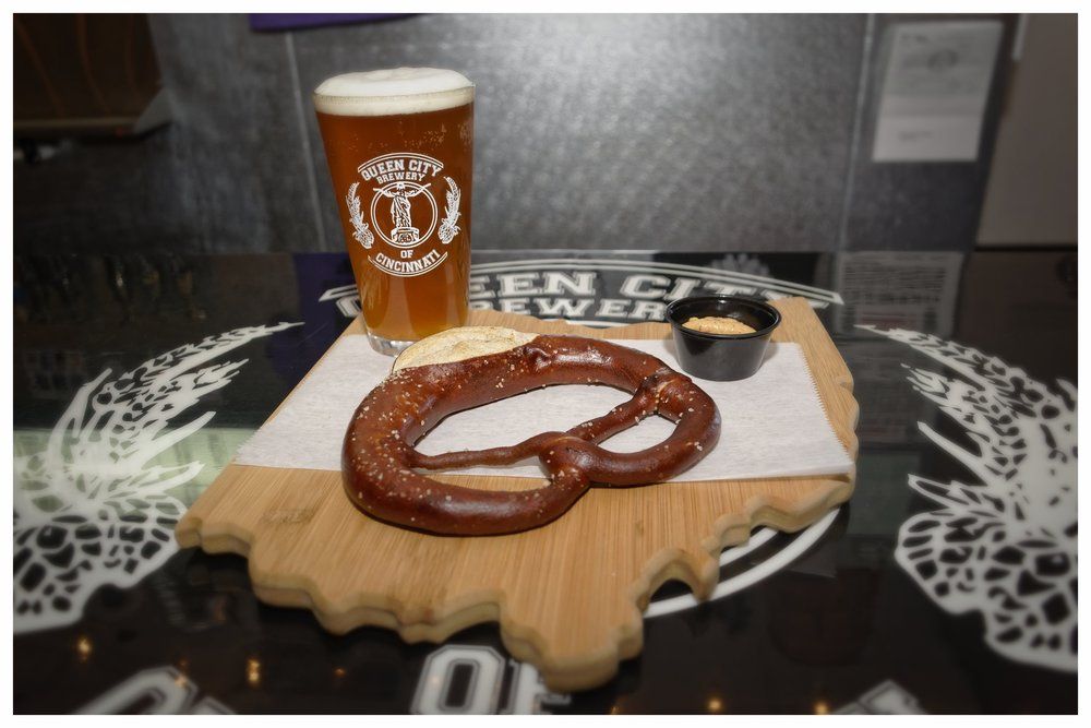 Swabian Style Hot Pretzel- $6 - An authentic German pretzel, cooked local from Tuba Baking Co. Having both soft and crispy pretzel bits, it's one all around snack. Served with QCB beer cheese or mustard.