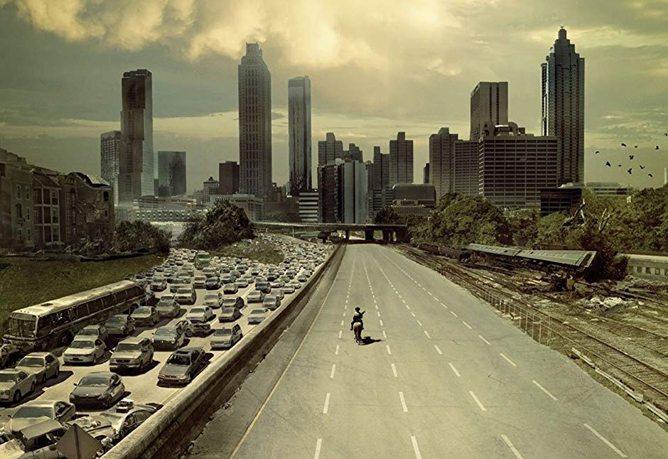 The Walking Dead Season 1 poster depicts Rick Grimes riding his horse down an empty highway toward Atlanta Georgia