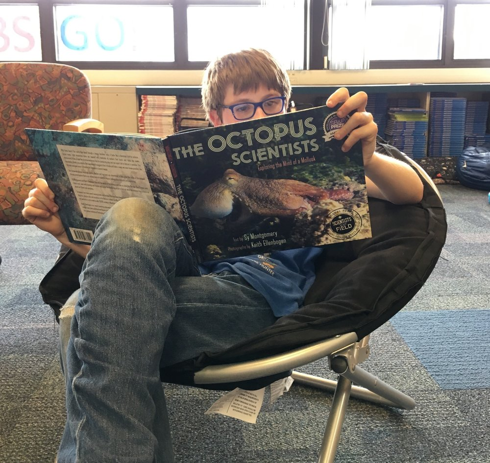 A student at Oliver McCracken Middle School enjoys  The Octopus Scientists, Exploring the Mind of a Mollusk , donated by Evanston Subaru in 2016. Photo used with permission.