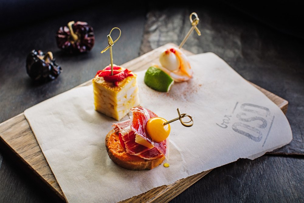 Pintxos—bites of flavors like  Bar Oso 's iberico ham, manchego cheese and tomato skewered together with a piece of bread—are classic Basque bar food.  Kevin Clark | Courtesy Toptable Group