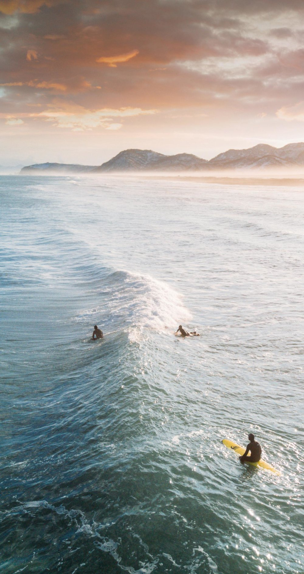 surfin at dawn pexels license https://www.pexels.com/photo/view-of-three-people-surfing-1553959/