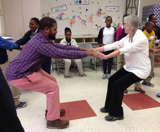 Workshop leader and dancer,  Diana Green  (r.) practices weight sharing and balance with a fifth-grade teacher as  students observe and participate.