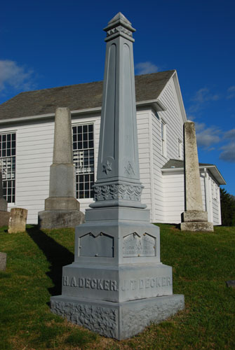 This is a metal obelisk which is in a class by itself. Ordered from mail order companies such as Sears & Roebuck, the cast iron had distinct advantages and disadvantages as a material for memorials. On the credit side they afforded durablity, easy and cheap manufacturing, and the freedom to create new designs, which was impossible to do in stone. Disadvantages included the essentially repetitive process of making them, and the difficulty of adding further lettering once the design had been cast.