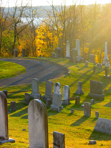 Much depends upon the layout of the graveyard. If there were a church-chapel in the center of the cemetery on high ground, the location of access roads was important. Early graves were seldom in the neat rows that we are used to seeing today. Burials were more haphazard and irregular. With the coming of the Rural Cemetery Movement in the 1830s-1840s, an entirely new style of burial became popular. The ideal of winding roads and irregular terrain dictated the orientation of the monuments to a large degree.