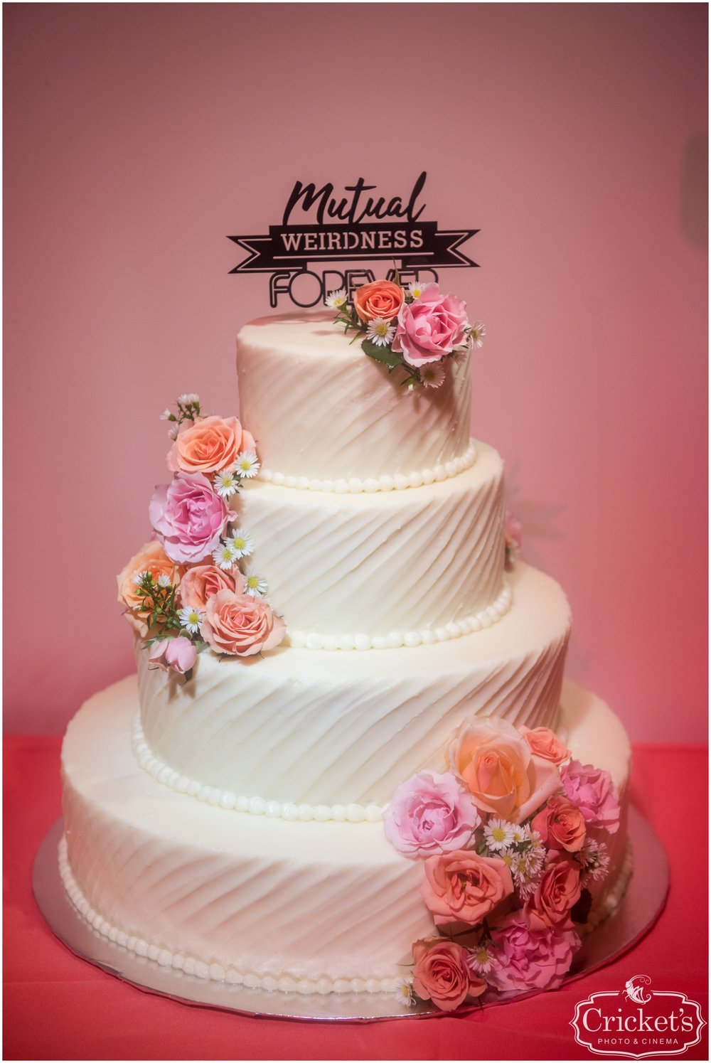 Pink floral and white wedding cake