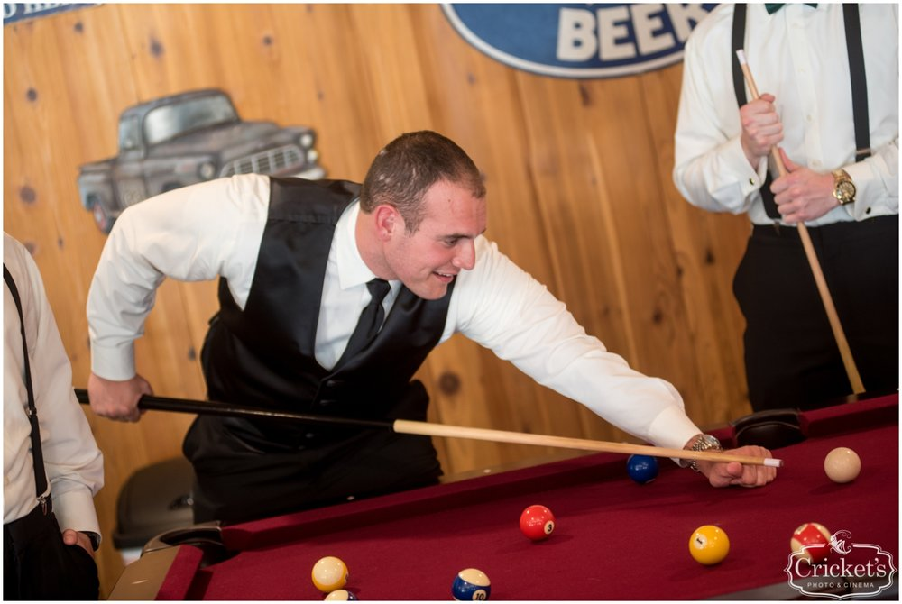 Groom playing pool with his groomsmen