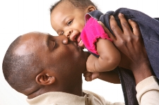 Dad kissing baby; how babies learn to talk at Canto Speech Therapy Online