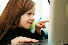 Girl pointing to computer; treat speech and language disorders, anyplace, worldwide, at Canto Speech Therapy Online