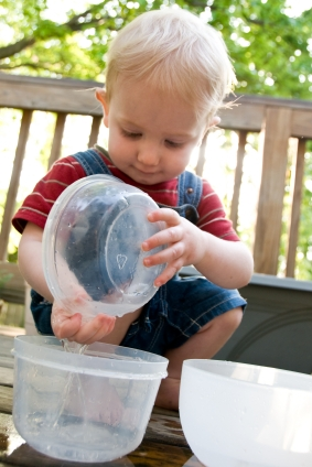 Boy playing with water in bowls; language activities at Canto Speech Therapy Online