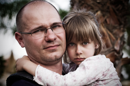 Worried dad holding girl with phonological speech disorder at Canto Speech Therapy Online