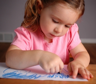 Little girl scribbling; early writing is a pre-reading skill. Learn more at Canto Speech Therapy Online