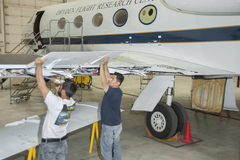 NASA aircraft technicians Leo and Juan Salazar work on installation of test instrumentation in preparation for installation of the experimental Adaptive Compliant Trailing Edge flap on NASA's modified G-III Aerodynamic Research aircraft.Credits: NASA / Ken Ulbrich