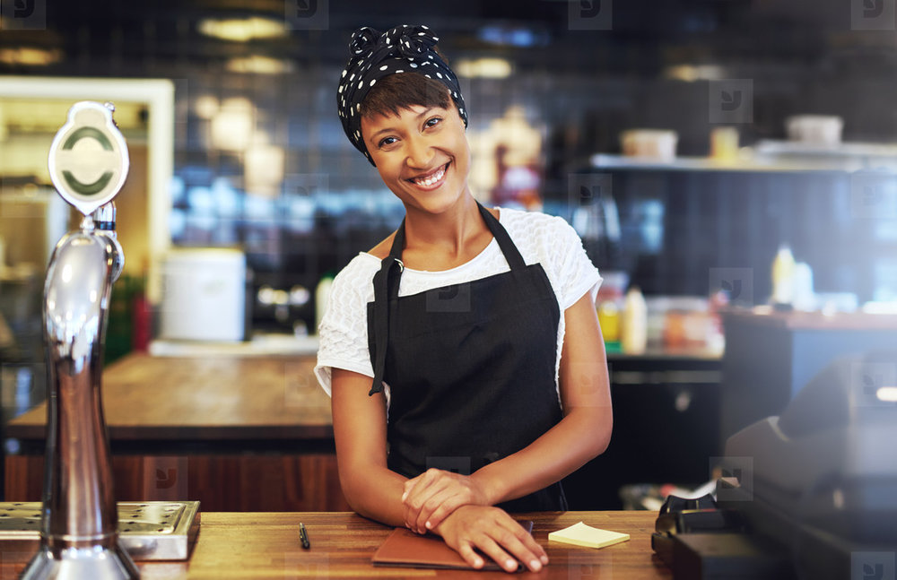 Business entrepreneur standing behind the counter in her cafe.