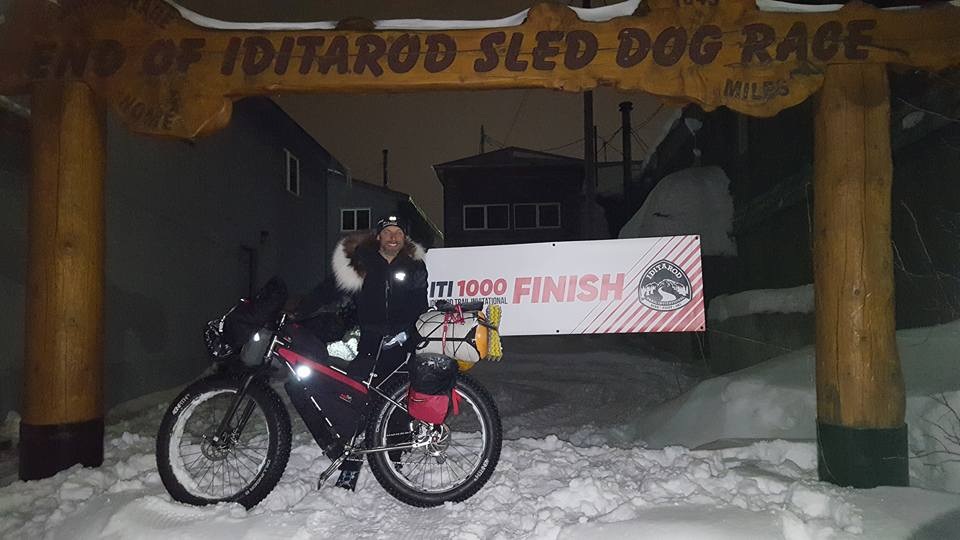 Kyle Durand under the Nome arch 1000 mile finish line