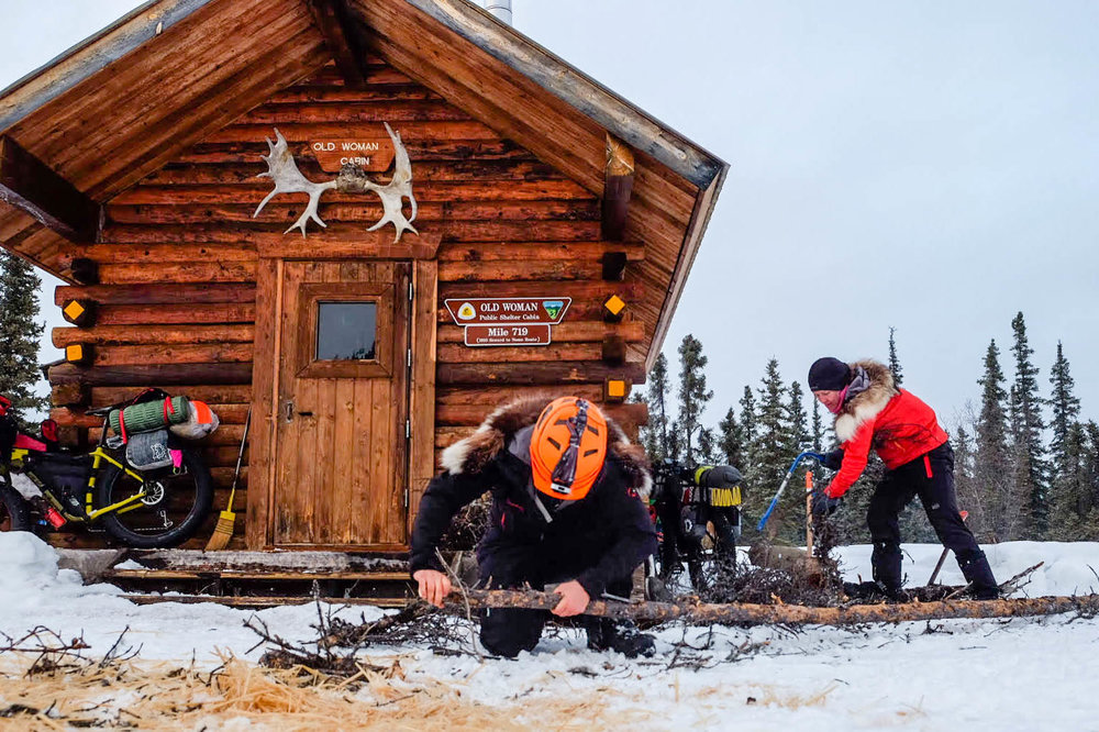 Missy and Kim prepare firewood at the Old Woman shelter cabin between Kaltag and Unalakleet 📷 Nicholas Carmen