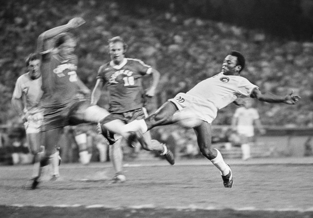 Pele #10 of the New York Cosmos takes a shot during an North American Soccer League (NASL) soccer match against the San Jose Earthquakes played on August 7, 1976 at Spartan Stadium in San Jose, California. Defending is Milo Pavlovic #21.  Photo by David Madison/Getty Images.