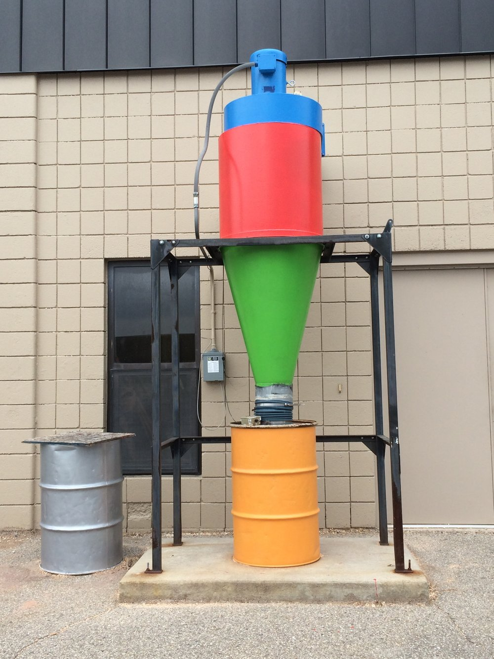 Look for the colorful dust collector! - Locating Maker Works within Airport Plaza industrial park can be challenging. Most of the buildings are beige, many navigation apps give the wrong directions, and signage is limited due to zoning regulations. We've painted our dust collector in fun Maker Works colors to brighten your day and help you find your way!Across from Costco, turn onto Plaza Drive, take the (quick) second left, and it's the third building on the right. The entrance is around the corner from the dust collector, on the right side of the building.