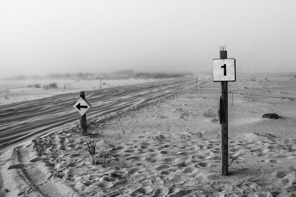 Black and white photo of the Outer Beach in Orleans, Mass. showing the off-road trail and signs with fog rolling in.