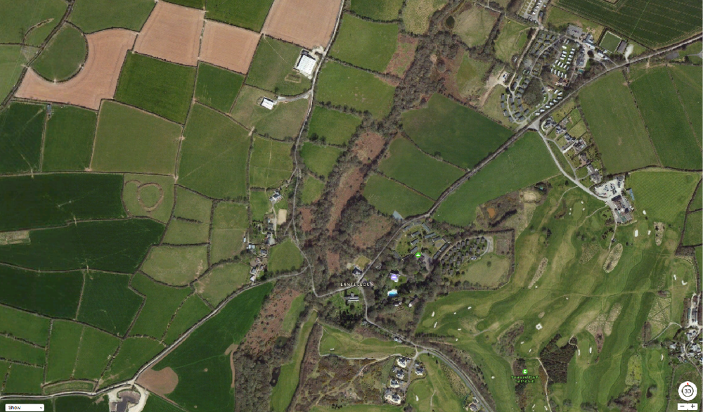Satellite view of Lanteglos showing iron age rounds on the left and 2 holiday sites. The river runs along the tree line and the holy well is near the top hidden by the trees.