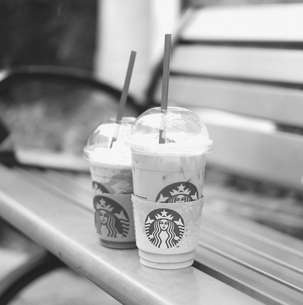 Starbucks iced drinks on a bench