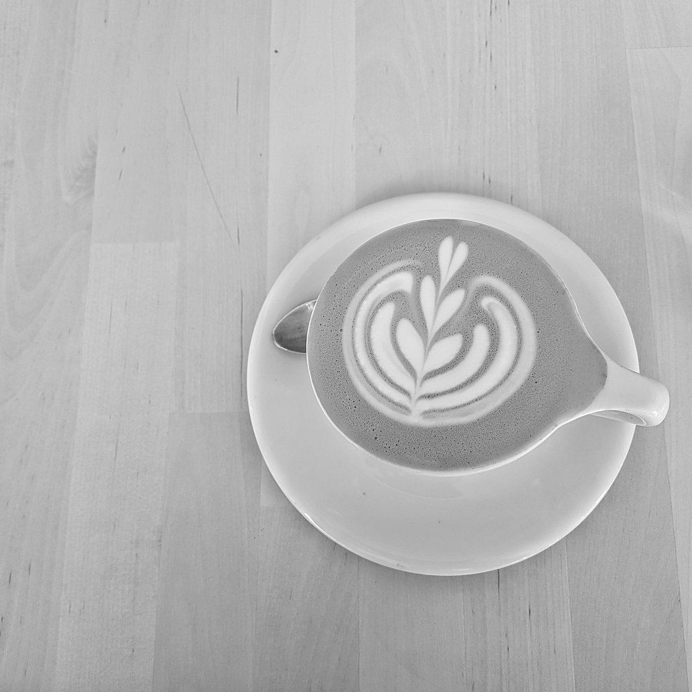 A latte from above sitting on a wooden table