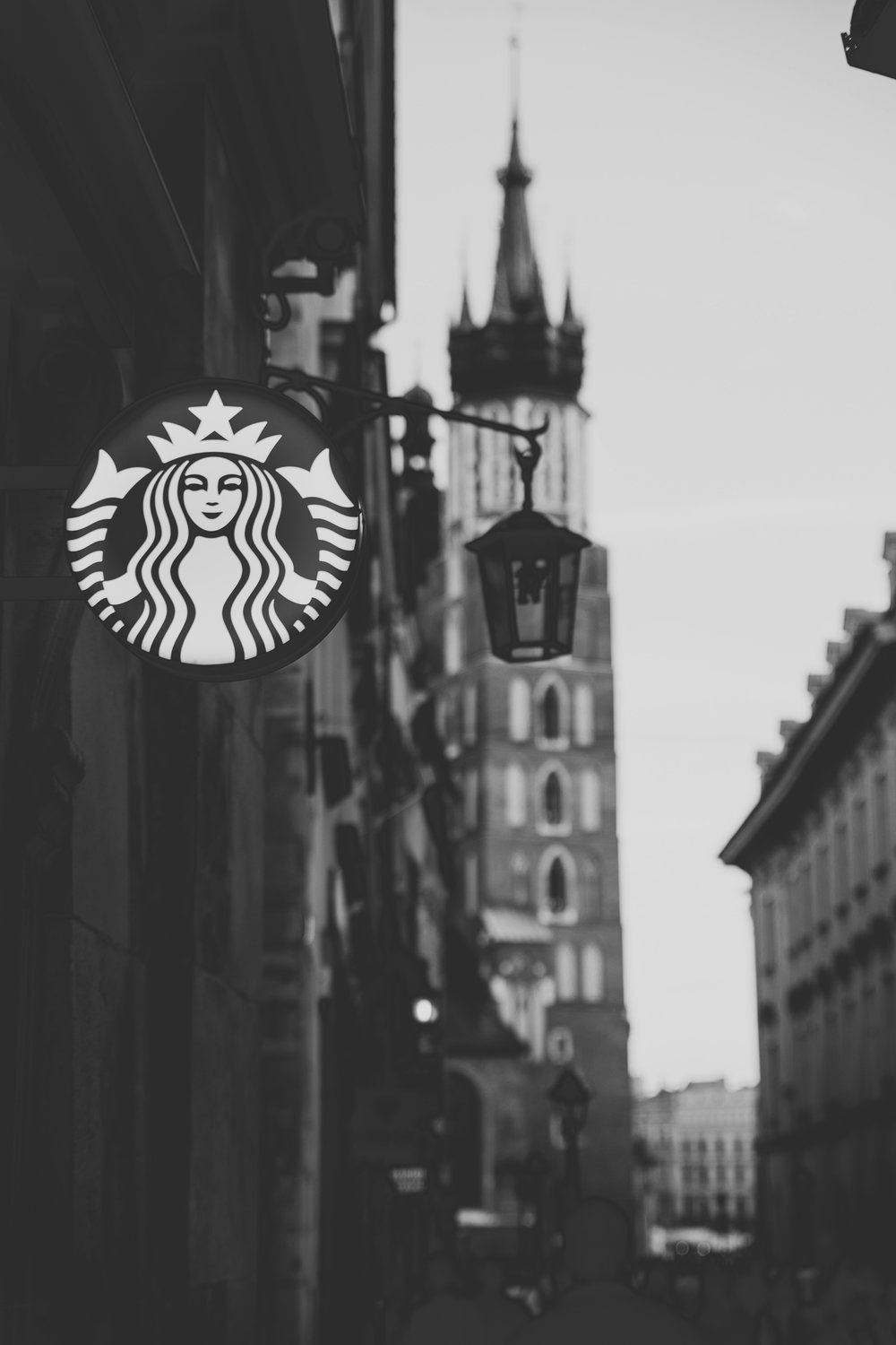 A Starbucks sign hangs in the foreground, with a medieval town out of focus behind