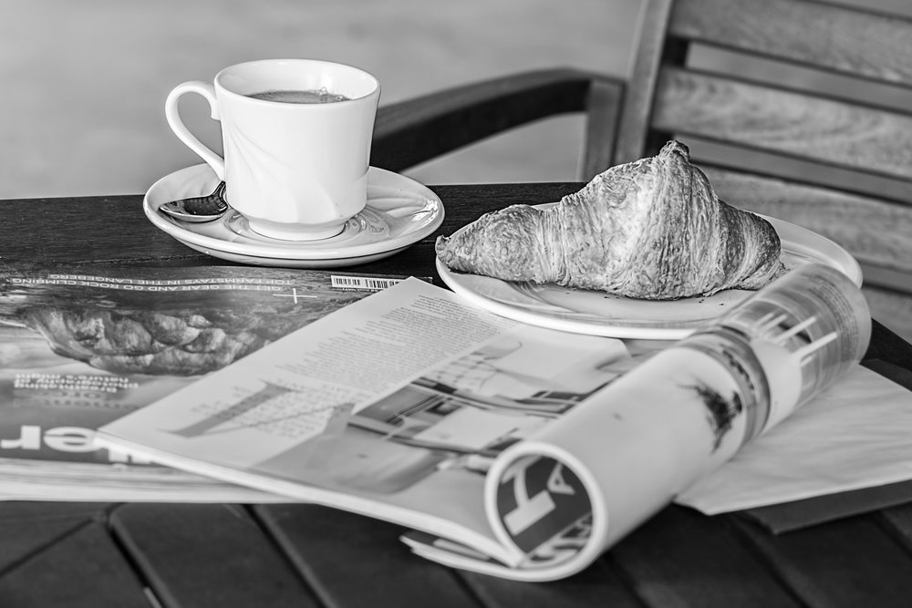 A coffee and a croissant on an open magazine atop a wooden table