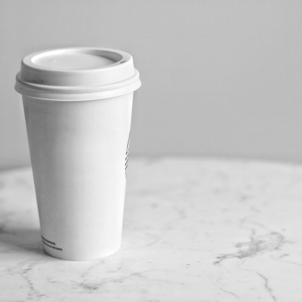 A white single-use coffee cup sits on a marble table.