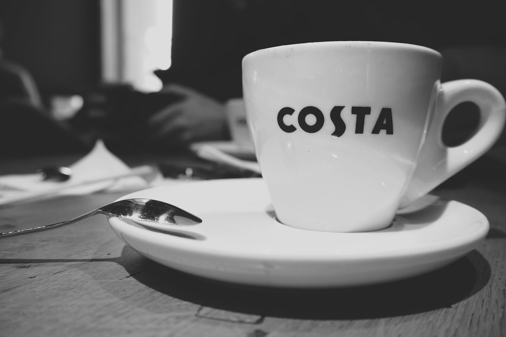 A Costa-branded coffee cup sits on a table