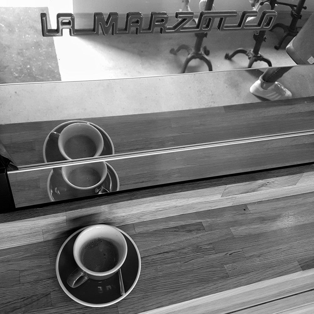 A shot of espresso sits on a counter in front of a shiny La Marzocco espresso machine