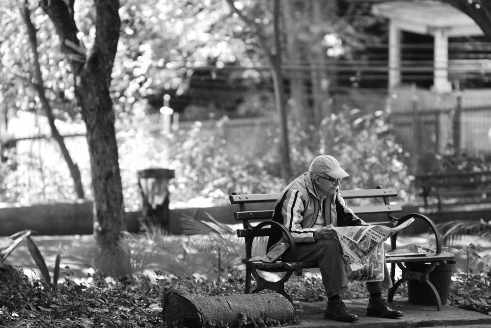 An old man reading a newspaper on a park bench