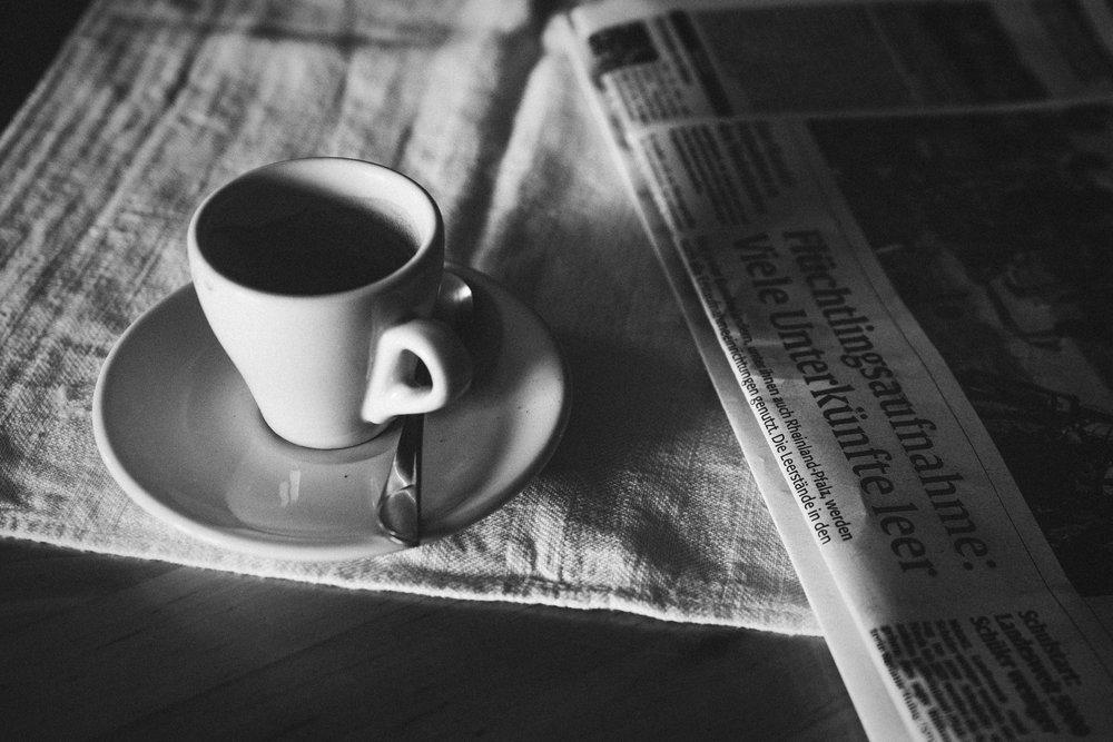 An espresso sits on a tablecloth beside a newspaper