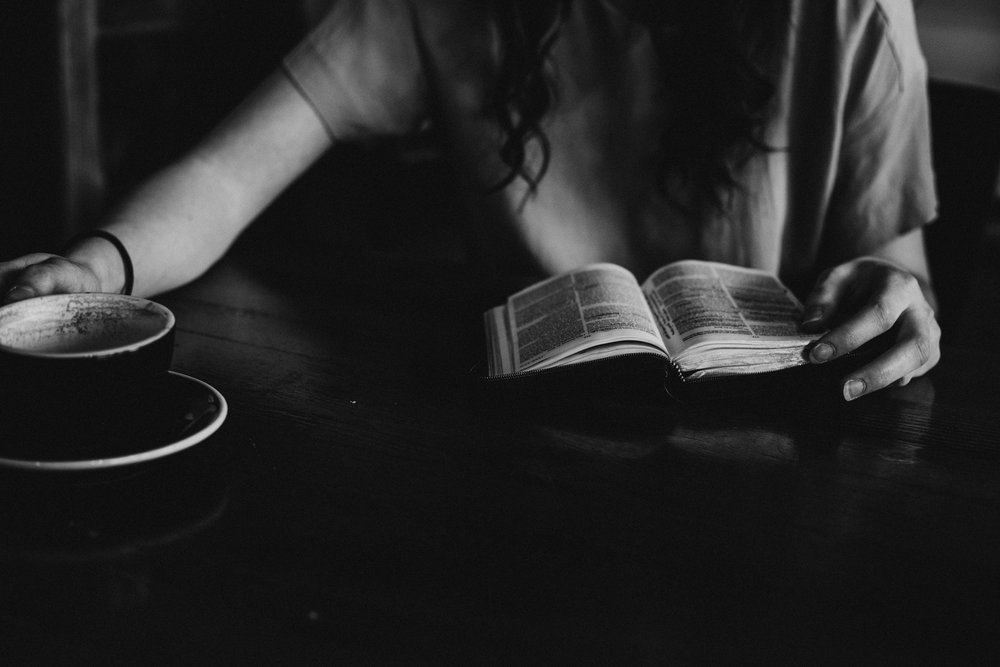 A woman reads a book at a table while reaching for a coffee
