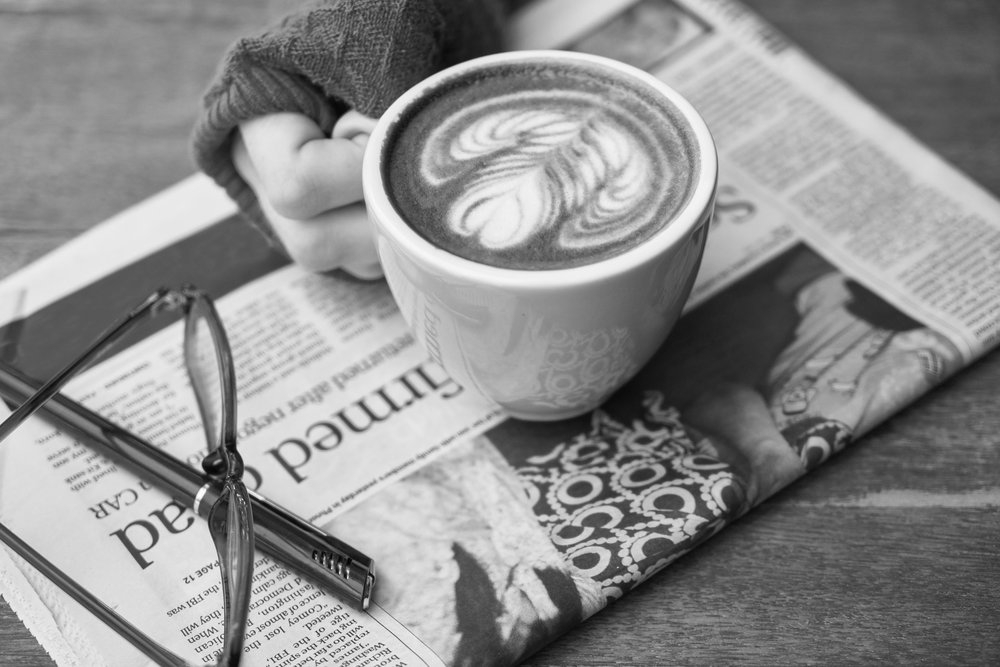 A hand holds a latte resting on a newspaper on a table.