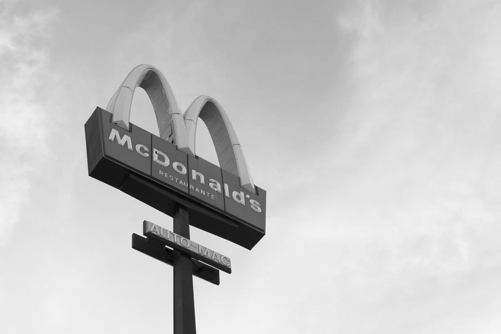 A McDonald's sign against a cloudy sky background