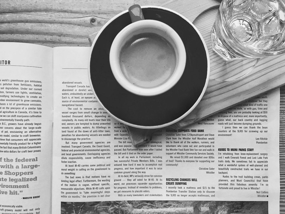 An espresso sits atop a newspaper, seen from above