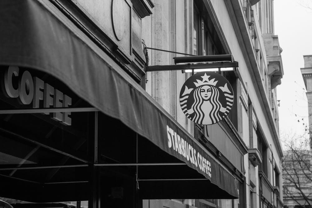 A Starbucks sign hangs above a shop