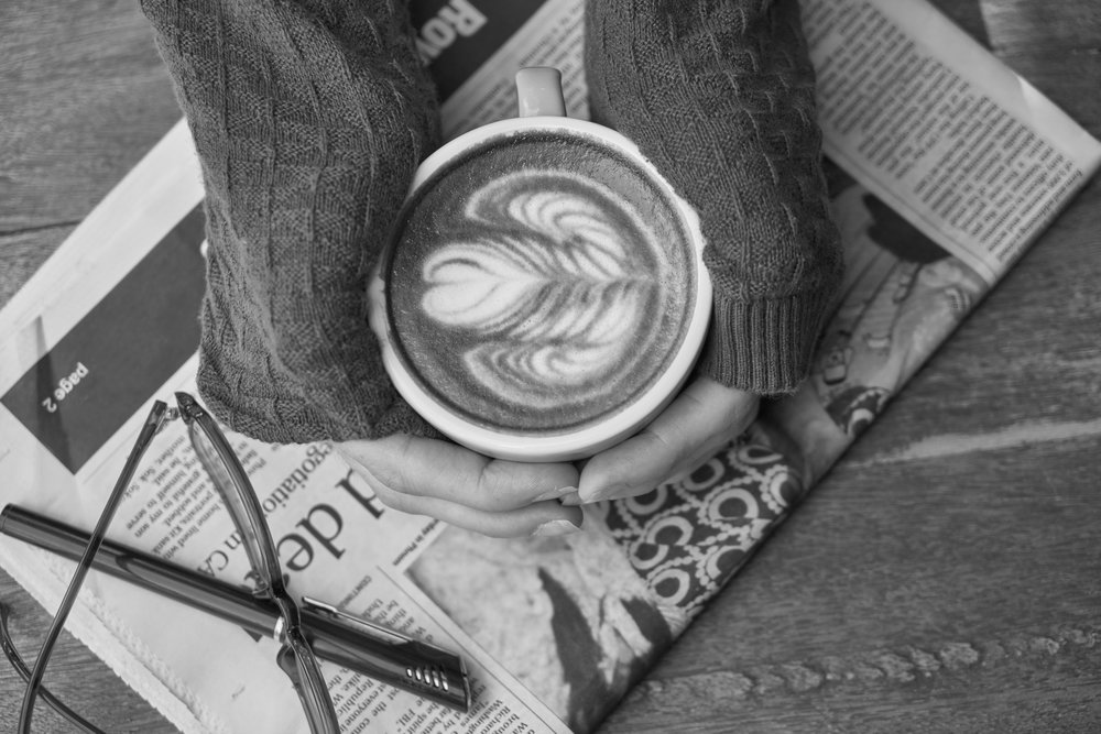 Two hands cupping a latte, resting atop a newspaper, seen from above.